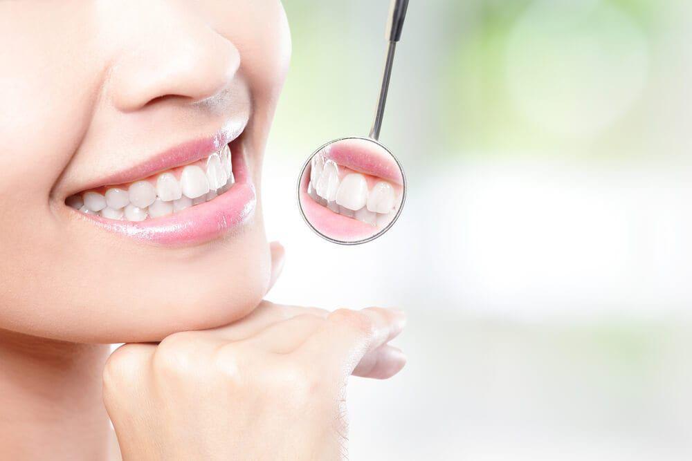 dental instrument examining smiling teeth